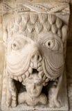 Monstruo o Tarasque que devora un románico del pecador c12th que talla en la abadía de Montmajour de los claustros cerca de Arles Foto de archivo libre de regalías