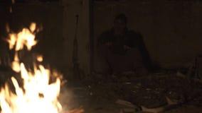 Monstruo peligroso feo del zombi que se sienta cerca de la hoguera con el rifle en refugio concreto arruinado oscuro Carácter del almacen de video