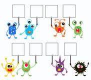 monstruos coloridos con los carteles Imagen de archivo