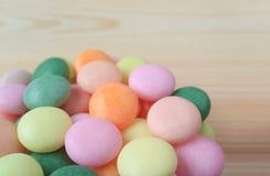 Montão ascendente fechado de doces redondos da cor pastel na tabela de madeira natural da cor clara Foto de Stock