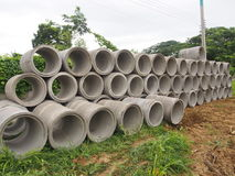 Montão das tubulações concretas da drenagem empilhadas no canteiro de obras com perspectiva de diminuição Imagem de Stock Royalty Free
