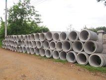 Montão das tubulações concretas da drenagem empilhadas no canteiro de obras com perspectiva de diminuição Fotos de Stock