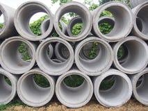 Montão das tubulações concretas da drenagem empilhadas no canteiro de obras com perspectiva de diminuição Foto de Stock