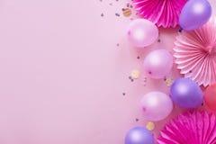 Montão de balões coloridos, de confetes e das flores de papel na opinião de tampo da mesa cor-de-rosa Fundo da festa de anos Cart fotos de stock