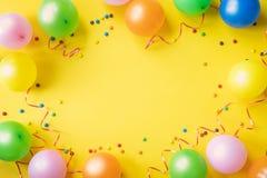 Montão de balões, de confetes e de doces coloridos na opinião de tampo da mesa amarela Fundo da festa de anos Cartão festivo imagens de stock