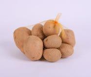 Montão de batatas cruas no saco de corda amarelo Imagem de Stock
