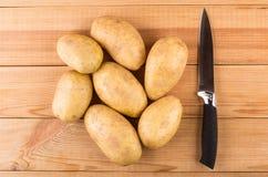 Montão de batatas e da faca de cozinha lavadas cruas Imagem de Stock