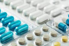 Montão de comprimidos médicos no branco, no azul e no cinza Comprimidos no pacote plástico Conceito dos cuidados médicos e da med Imagens de Stock