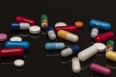 Montão de drogas e de comprimidos coloridos no fundo preto Fotografia de Stock Royalty Free