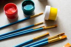 Montão de escovas da arte e de poucos frascos da pintura Fotos de Stock Royalty Free