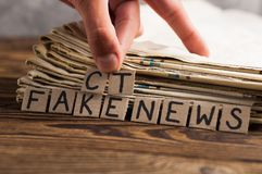 Montão de jornais velhos ao lado dos dedos e dos quadrados humanos do retângulo do cartão com a falsificação escrita à mão da ins imagens de stock royalty free