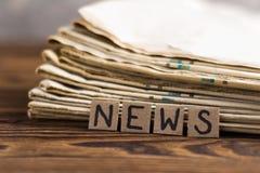 Montão de jornais velhos ao lado dos quadrados do retângulo do cartão com notícias escritas à mão da inscrição na tabela de madei foto de stock