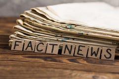 Montão de jornais velhos ao lado dos quadrados do retângulo do cartão com notícias escritas à mão do fato da inscrição na tabela  foto de stock