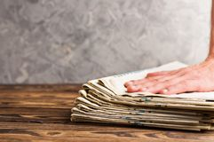 Montão de jornais velhos empilhados e da mão humana na tabela de madeira marrom velha imagens de stock royalty free