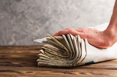 Montão de jornais velhos empilhados e da mão humana na tabela de madeira marrom velha foto de stock