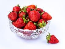 Montão de morangos maduras frescas na bacia de vidro no fundo branco, isolado Foto de Stock