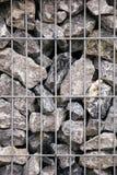 Montão de pedras cinzentas atrás da estrutura do metal Fotos de Stock Royalty Free