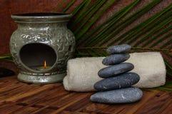 Montão de pedras quentes dos termas para a massagem com a lâmpada do aroma no fundo de madeira Fotografia de Stock