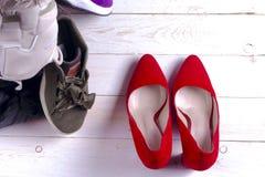Montão grande de sapatas diferentes dos esportes e de sapatas vermelhas do ` s das mulheres do salto alto no fundo branco Fotos de Stock