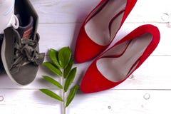 Montão grande de sapatas diferentes dos esportes e de sapatas vermelhas do ` s das mulheres do salto alto no fundo branco Foto de Stock Royalty Free
