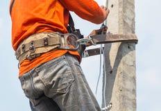 Montée d'électricien fonctionnant dans la taille sur le poteau avec la ceinture de sécurité image libre de droits