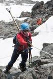 Montée d'alpiniste de ski de jeune femme sur la corde sur des roches Images libres de droits