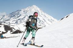 Montée d'alpiniste de ski de jeune femme sur la montagne sur le volcan de fond Image stock