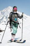Montée d'alpiniste de ski de jeune femme sur la montagne sur le volcan de fond Images stock