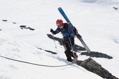 Montée d'alpiniste de ski sur la corde sur des roches Images stock