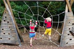 Montée d'enfants sur le terrain de jeu de cour d'école Photos libres de droits