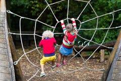 Montée d'enfants sur le terrain de jeu de cour d'école Images stock