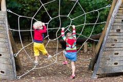 Montée d'enfants sur le terrain de jeu de cour d'école Photographie stock libre de droits