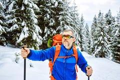 Montée d'hiver jusqu'au dessus de la montagne avec un sac à dos Images libres de droits