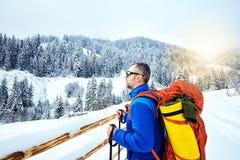 Montée d'hiver jusqu'au dessus de la montagne avec un sac à dos Photos stock