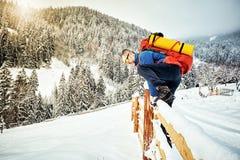 Montée d'hiver jusqu'au dessus de la montagne avec un sac à dos Image libre de droits