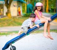 Montée de garçon sur la glissière avec la soeur Photos stock