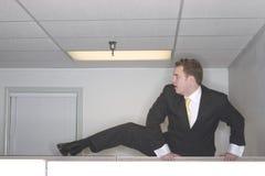 Montées d'homme d'affaires au-dessus de cubicl Image stock