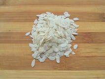 Montón aplanado del arroz en fondo de madera fotos de archivo libres de regalías