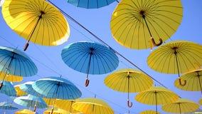 Montón azul y amarillo del paraguas en el cielo azul en día soleado, almacen de video