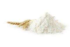 Montón de la harina de trigo con las espiguillas aisladas en blanco Foto de archivo libre de regalías