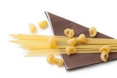 Montón de las cáscaras y de los espaguetis de los macarrones en servilleta marrón Imágenes de archivo libres de regalías