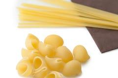 Montón de las cáscaras y de los espaguetis italianos de los macarrones en servilleta marrón Imágenes de archivo libres de regalías