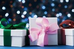 Montón de las cajas o de los presentes de regalos contra fondo azul del bokeh Tarjeta de felicitación de la Navidad del día de fi Fotografía de archivo