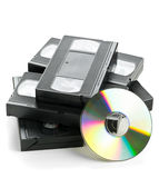 Montón de las cintas de video análogas con el disco del DVD Imagen de archivo libre de regalías
