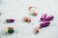Montón de las píldoras de la medicina en el papel de la rejilla del cardiograma Imágenes de archivo libres de regalías