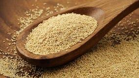 Montón de las semillas crudas, crudas del amaranto en la cucharada de madera que gira almacen de video