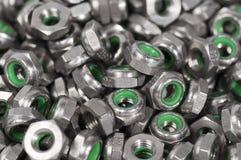 Montón de las tuercas del metal con el interior verde Fotos de archivo
