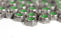 Montón de las tuercas del metal con el interior verde Imágenes de archivo libres de regalías