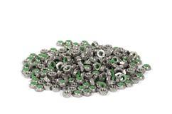 Montón de las tuercas del metal con interior verde, empilado, aislado en blanco Foto de archivo libre de regalías