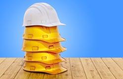 Montón de los cascos marrones de los trabajadores y casco blanco de un ingeniero o de un capataz en la tabla de madera, represent libre illustration